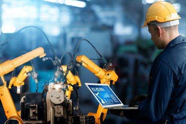 pracownik fabryki obsługujący robota